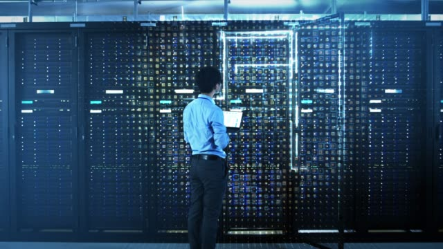 stockvideo's en b-roll-footage met het concept van digitalisering van informatie: it-specialist staande voor server racks met laptop, activeert hij data center met een touch gebaar. animated visualisatie van het netwerk van data blokken verspreiden - datacenter