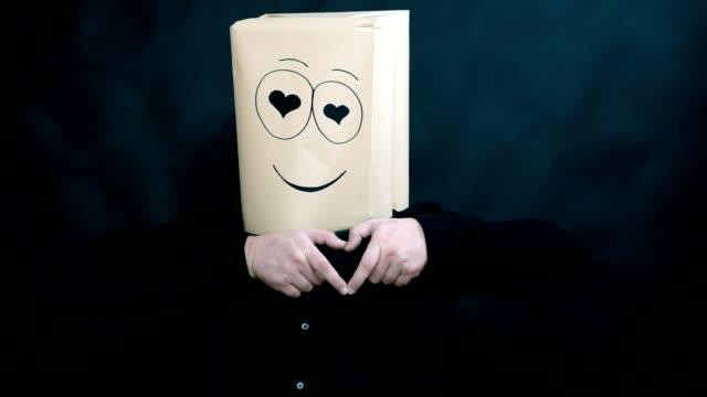 stockvideo's en b-roll-footage met het concept van emoties. a man zijn vingers beeldt een vorm van een hart. liefhebbers ogen kijkt. kus van de lucht. - menselijke vinger