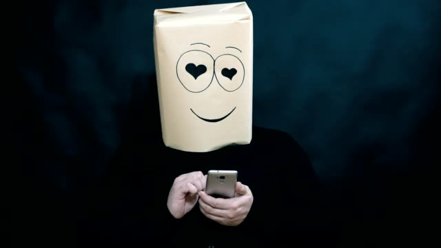 The concept of emotions. The man on the smart phone displays the image of a loved one. Looking lovers eyes. Kisses the image. On the face a smile and happiness. The background is dark blurred.