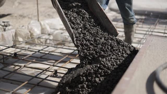 il mix di calcestruzzo viene alimentato da una betoniera. cementificazione. pavimento in cemento. - cemento video stock e b–roll