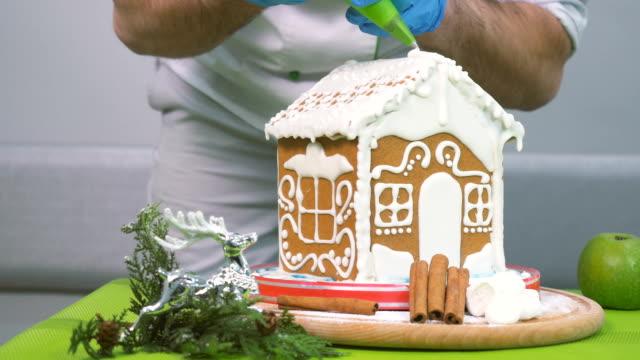 der konditor dekoriert das lebkuchenhaus mit sahne - lebkuchenhaus stock-videos und b-roll-filmmaterial
