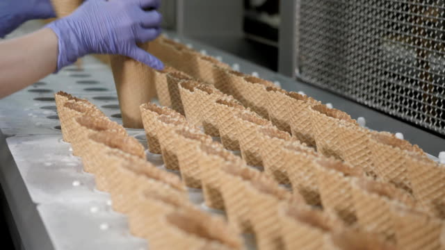 the conveyor automatic lines for the production of ice cream cones. wafer cups and cones. large industrial production. a major supplier of ice cream to the retail network - gelato confezionato video stock e b–roll