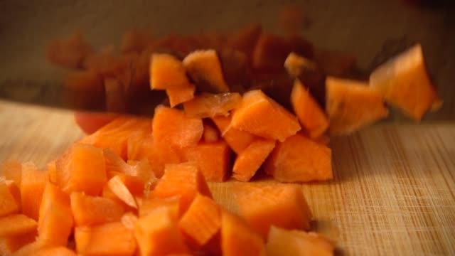 kocken skär morötter med en kniv. slow motion. - morot bildbanksvideor och videomaterial från bakom kulisserna