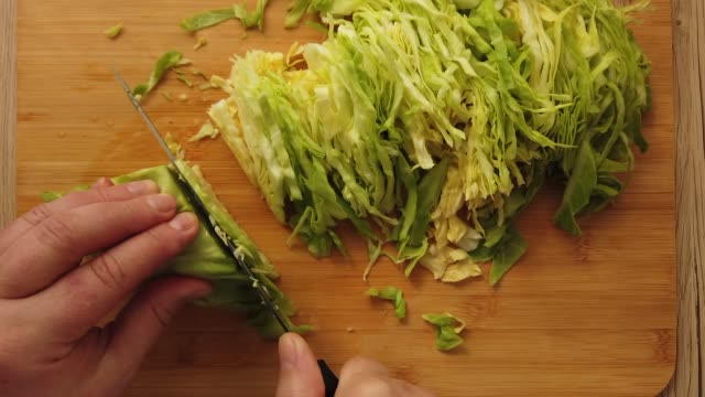 The cook cuts the cabbage on the cutting board. video