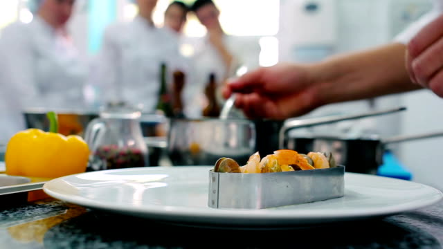 The cook decorating the dish in the restaurant video