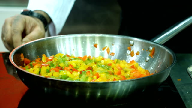 The cook fry the vegetables in a frying pan. video