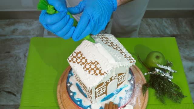 der koch schiebt eine weiße sahne aus sahne-injektor auf das lebkuchenhaus - lebkuchenhaus stock-videos und b-roll-filmmaterial