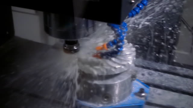 The cooling liquid is poured on the detail on the milling machine. Slow mo The fluid cools the machined part on a milling machine. Slow motion, high speed camera, 250fps metal worker stock videos & royalty-free footage