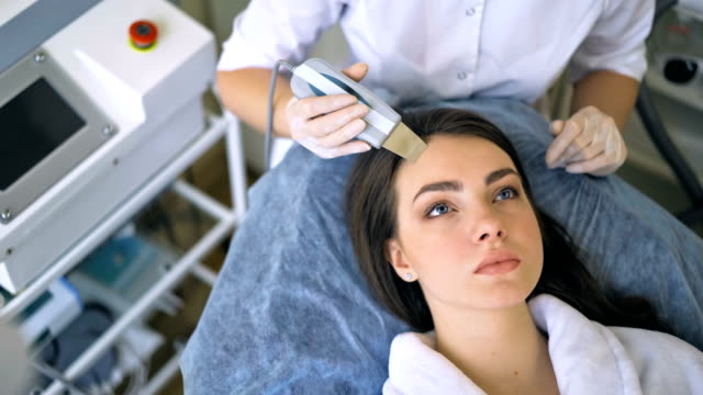 The cosmetologist makes the procedure ultrasonic face peeling of the facial skin of a beautiful, young woman in a beauty salon video