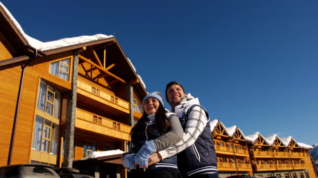 The couple enjoys a clear winter day on a background of a wooden cottage.