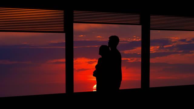 the couple hugs near the window on a bright sun background. time lapse - man look sky scraper video stock e b–roll