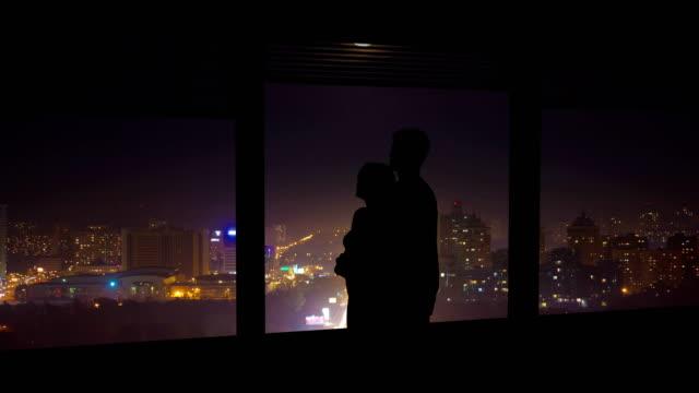 the couple hugs near the window on a night city background. time lapse - man look sky scraper video stock e b–roll