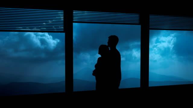 the couple hugs near the window on a night mountain background. time lapse - man look sky scraper video stock e b–roll