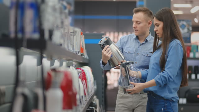 The couple in casual clothes in the electronics store chooses an electric kettle for their kitchen, holding in their hands and reading and reading the price tags with the characteristics The couple in casual clothes in the electronics store chooses an electric kettle for their kitchen, holding in their hands and reading and reading the price tags with the characteristics. appliance stock videos & royalty-free footage