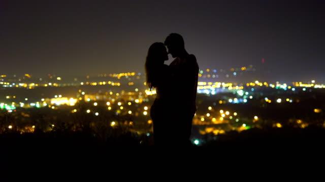 vídeos y material grabado en eventos de stock de la pareja besándose en el fondo de las luces de la ciudad. noche - deseo