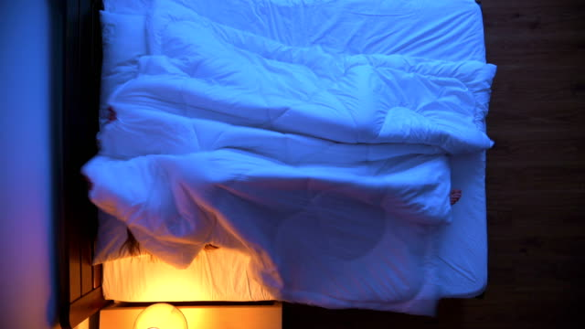 The couple playing under the duvet on the bed. evening night time