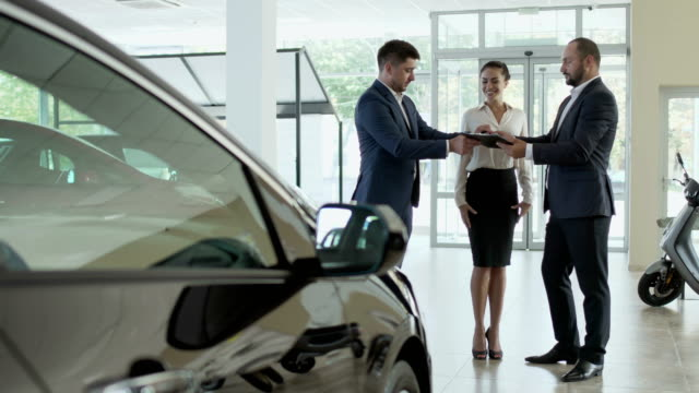 The couple signs the contract of buying car in the car showroom and gets key Young couple is buying a new car in the car dealership. Handsome businessman signs the agreement and gets a keys from car from salesman. The men shakes hands and businessman gives a keys to his wife. Happy woman smiles and hugs with her husband. car rental stock videos & royalty-free footage