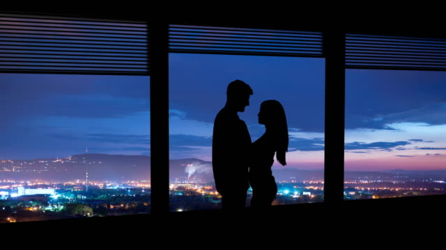 the couple stand near the window on a city lights background. time lapse - man look sky scraper video stock e b–roll