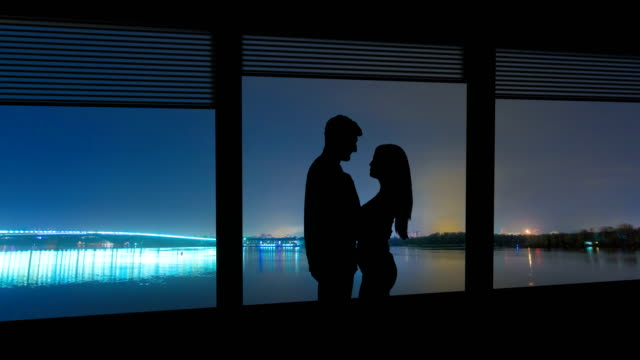 the couple stand near the window on a city river background. time lapse - man look sky scraper video stock e b–roll
