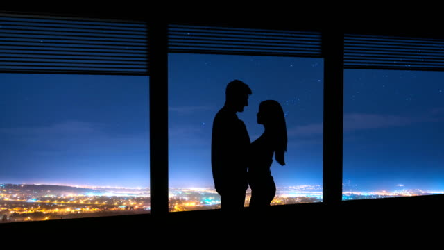 the couple stand near the window on a night city background. time lapse - man look sky scraper video stock e b–roll