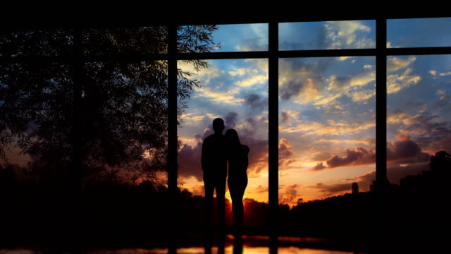 the couple standing near panoramic windows on a sunset background. time lapse - man look sky scraper video stock e b–roll