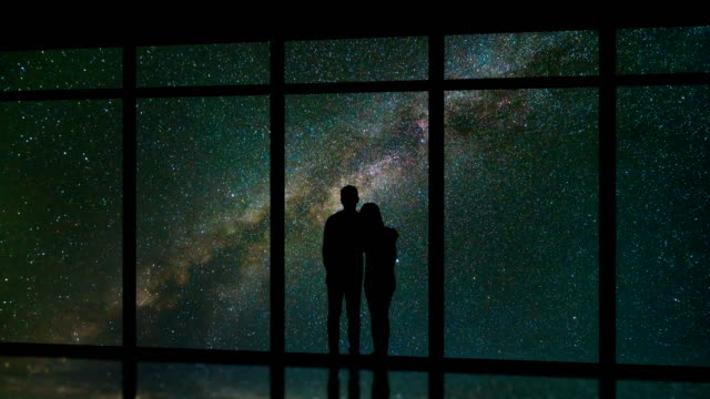 the couple standing near windows on the meteor shower background. time lapse - man look sky scraper video stock e b–roll