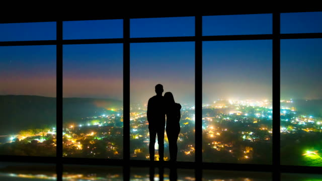 the couple standing near windows on the night city background. time lapse - man look sky scraper video stock e b–roll