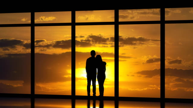 the couple standing near windows on the sunset background. time lapse - man look sky scraper video stock e b–roll
