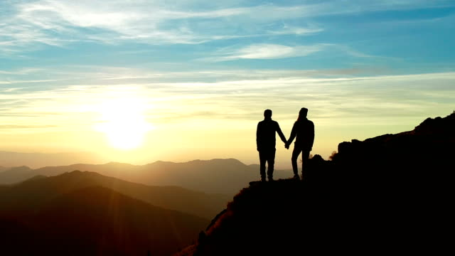 The couple standing on the mountain and watching to a beautiful sunrise