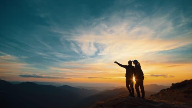 일몰 배경에 산에 서있는 부부 - 언덕 스톡 비디오 및 b-롤 화면