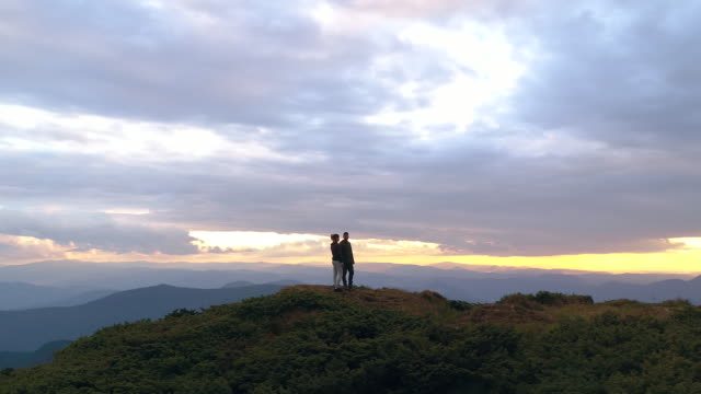The couple standing on the top of a mountain on a sunrise background