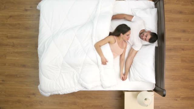 The couple talk in the bed. view from above