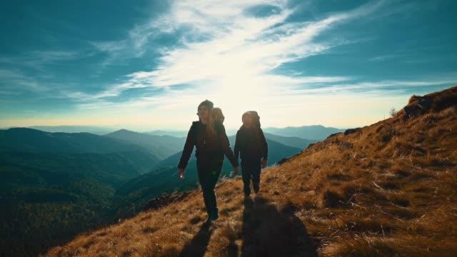 부부는 저녁 산을 따라 걷고. 슬로우 모션 - 이성 커플 스톡 비디오 및 b-롤 화면