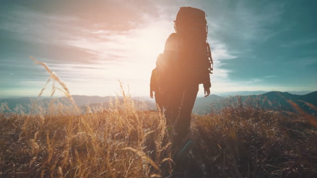 the couple walking in mountains on the sunny background. slow motion - trekking video stock e b–roll