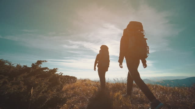 the couple walking in the mountain on the sunny background. slow motion - турист с рюкзаком стоковые видео и кадры b-roll