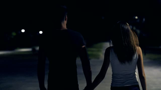 The couple walking in the night park. slow motion