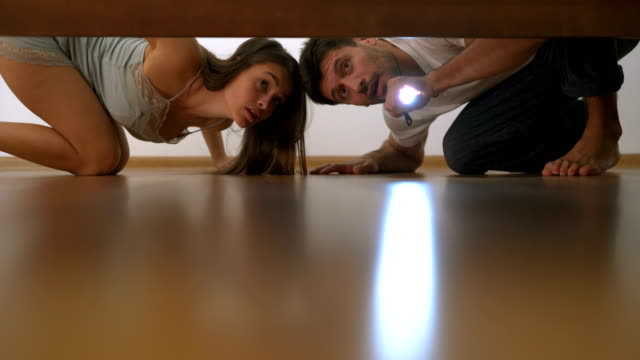 The couple with a flashlight looking under the bed