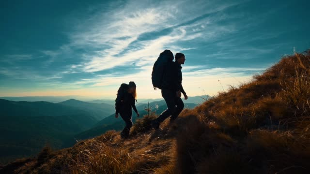 the couple with camping backpacks walking to the mountain top. slow motion - trekking video stock e b–roll