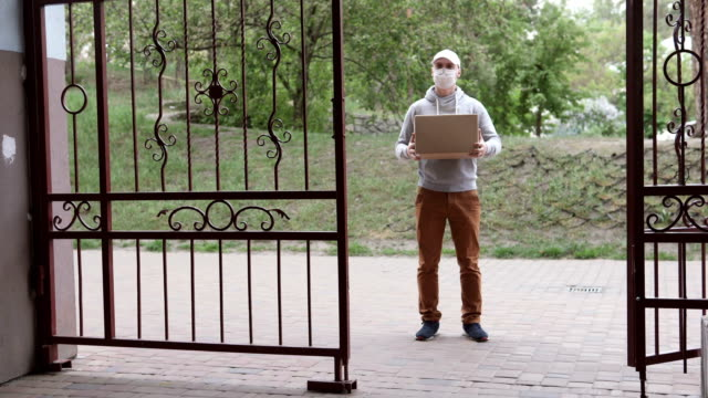 The courier delivers the package on the doorstep of the house. Food delivery during a pandemic, coronavirus. - vídeo