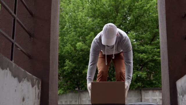 kurye paketi evin kapısına teslim ediyor. salgın sırasında yiyecek dağıtımı, koronavirüs. - sahanlık stok videoları ve detay görüntü çekimi