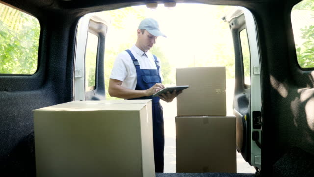 the courier use a digital tablet standing next to the van - furgone video stock e b–roll