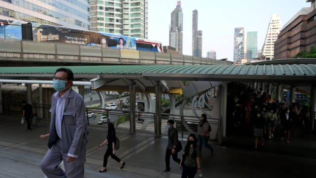 the crowd is wearing protective masks prevent coronavirus, covid 19 virus during virus outbreak and pm2.5 air pollution crisis rush hour in business center area, bangkok, thailand - businessman covid mask video stock e b–roll