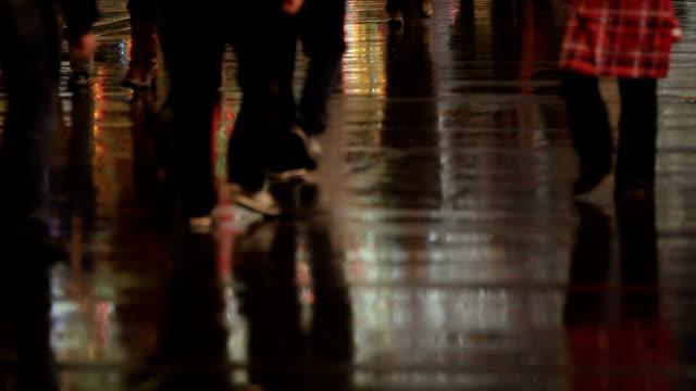 la folla di persone per le strade della città di notte. molti piedi in acqua e l'asfalto. - arto inferiore animale video stock e b–roll
