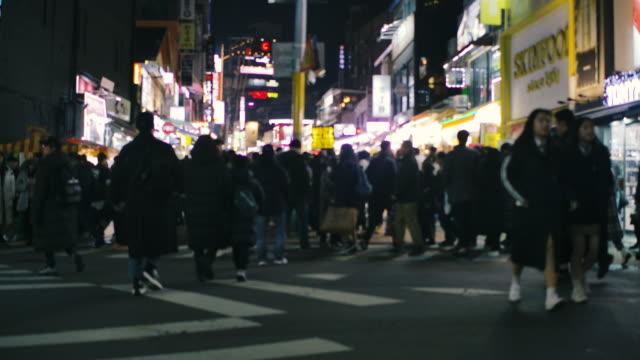 夜の韓国の都市生活の中で忙しい商店街を歩く人々の群衆 ビデオ