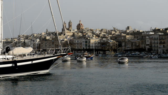 The cruise Luzzu boat swimms by and  yacht marina, Birgu, Malta video