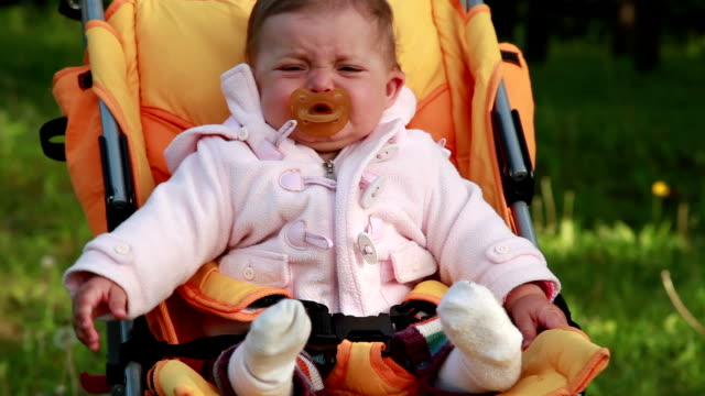 the crying baby sitting in the pram in the park - ciuccio video stock e b–roll