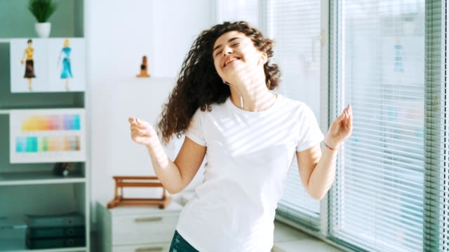 The curly girl in earphones dancing near the window. slow motion