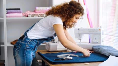 vidéos et rushes de la couturière bouclée travaillant avec un textile sur la table - fait maison