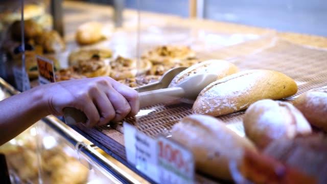 슈퍼마켓에서 빵집을 선택 하는 고객 - 식빵 한 덩어리 스톡 비디오 및 b-롤 화면