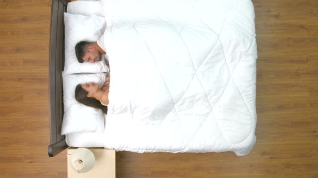 The cute couple lay in the bed. view from above